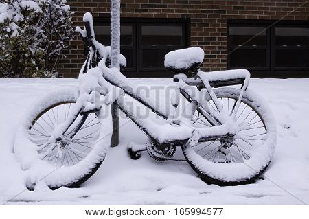 Full view of a bicycle covered in freshly fallen snow locked to a sign pole on a street in Montreal Quebec on a bright November day.