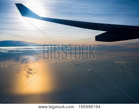 Flight over ocean with splashes of orange reflections caused by the sun, and flares caused by imperfections in the plane's window and internal reflections.