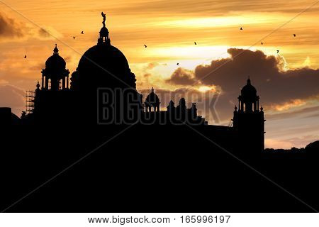 Victoria Memorial architectural building monument and museum in silhouette at sunset with a vibrant sky.
