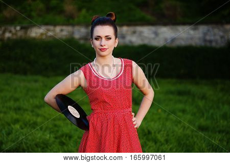 Portrait Of Young Pinup Girl Wearing At Retro Vintage Old-fashioned Dress In Peas With Vinyl Audio R