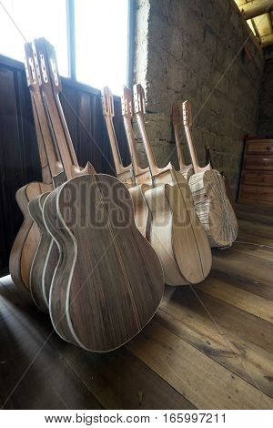 July 22, 2016 San Bartolome, Ecuador: unfinished classical guitars leaning against the wall in a small rural luthier shop