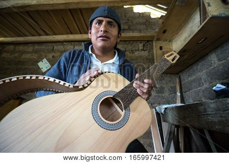 July 22, 2016 San Bartolome, Ecuador: an indigenous luthier holds up an unfinished guitar in his small rural shop