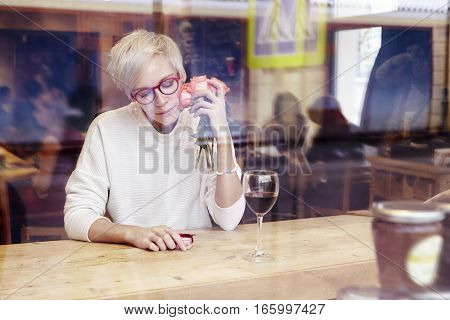 Blonde woman with short hair and eye glasses sitting in a cafe or restaurant near window. Romantic mood present and flowers in hand. Valentine's day concept