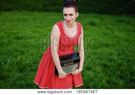 Portrait Of Young Pinup Girl Wearing At Retro Vintage Old-fashioned Dress In Peas With Retro Radio I