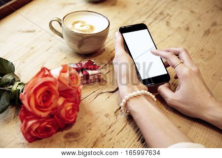 Mobile phone in beautiful woman hands. Lady writing message. Red roses flowers and present box behind on wooden table. St. Valentine's day concept