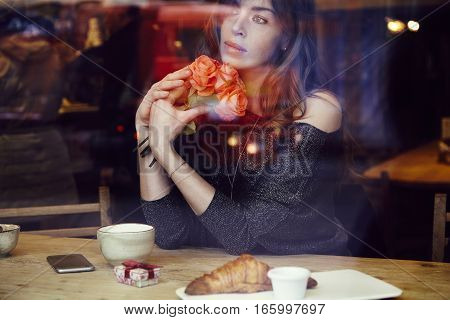 Beautiful woman with long hair holding red roses flowers in hand look through the window in cafe. Coffee and croissant on wooden table. St. Valentine's Day or Birthday concept.