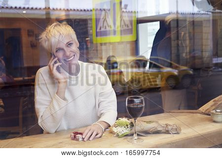Beautiful blonde woman talking by mobile phone in cafe. Romantic breakfast for a date or St. Valentine's Day. Present box and rose flowers.