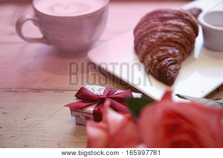 Romantic breakfast for Valentine's Day celebrate. Present box rose flowers fresh croissant coffeeon wooden table. Focuse at box