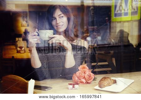 Beautiful caucasian woman with long hair near window in cafe celebrating present box and rose flowers. St. Valentine's Day concept or Birthday