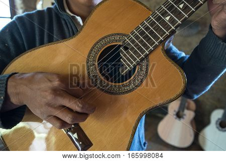 July 22, 2016 San Bartolome, Ecuador: a luthier holds up a finished guitar in his small rural shop