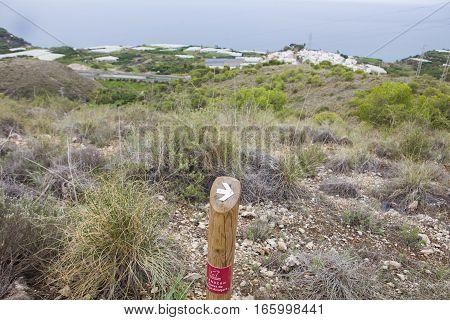 Nerja Spain - December 5 2016: Hiking sign at trekking path over Nerja Caves Mountain. Overlooking Town of Nerja Malaga Spain