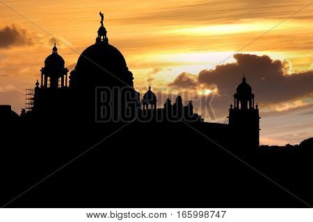Silhouette Victoria Memorial architectural building India with a vibrant sunset sky.