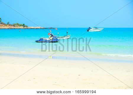 Boat in crystal turquoise sea on Koh Samet island in Thailand. Perfect beach getaway in warm tropical country
