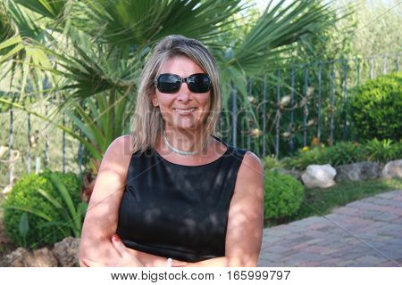 Blonde happy smiling Caucasian woman dressed in black with black sunglasses in outdoor gardens.