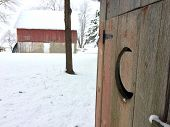 First snowfall and a 100 year old barn and a decorative outhouse door in rural Illinois. poster