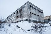 Exterior of housing of old decayed abandoned prison in Kolyma poster