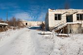 Abandoned prison settlement with decayed buildings in Northern Kolyma winter view poster