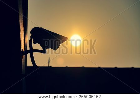 Silhouette Of Cctv Security Camera Outside Of Building In The Morning With Sun Background