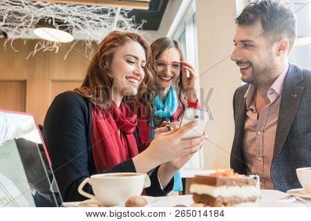 Three young colleagues or friends smiling while using a mobile phone for fun on social media during a coffee break in a trendy cafeteria