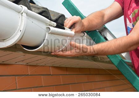 Gutter pipeline installation. Roofer contractor installing and repair rain gutter. Guttering repair with contractor hands. poster