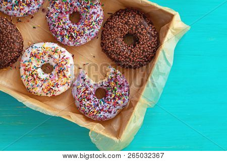 Delicious Glazed Donuts In Box On Turquoise Blue Surface. Flat Lay Minimalist Food Art Background. T