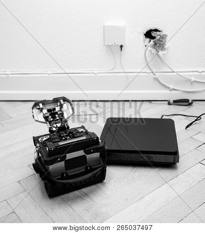 FTTH fiber installation at home with new arc clad-alignment fusion splicer used for splicing an array of thin optical fiber types with CATV on wall socket and tv internet receiver tuner black and white poster
