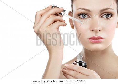 Woman applying Serum Extract at her skin.