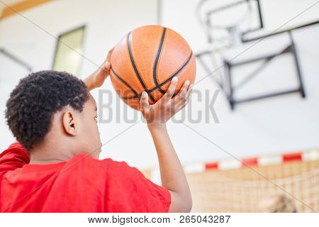 African boy with basketball in hand in front of the throw