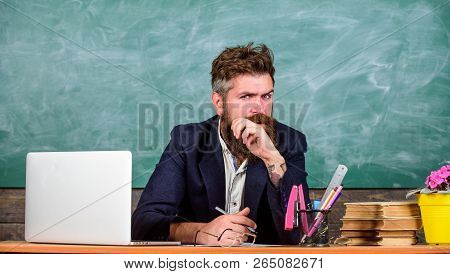 Not Sure In Knowledge. Examiner Full Of Doubts Sit At Table Chalkboard Background. Examiner Bearded