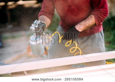 Construction Worker Painting Timber With Spraygun, Airgun. Carpentry Details
