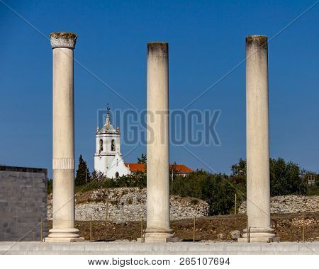 Church Framed By Roman Columns At  Conimbriga In Portugal Under A Cloudless Blue Sky