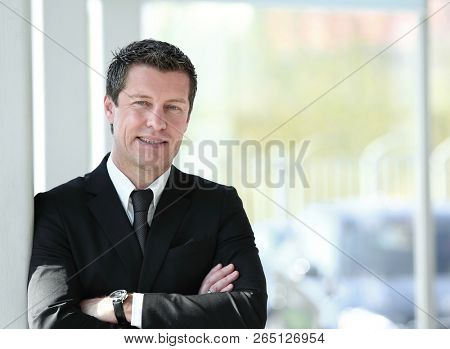 serious businessman standing near window in office.