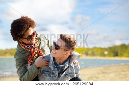 leisure and people concept - happy mixed-race teenage couple in sunglasses having fun over beach background