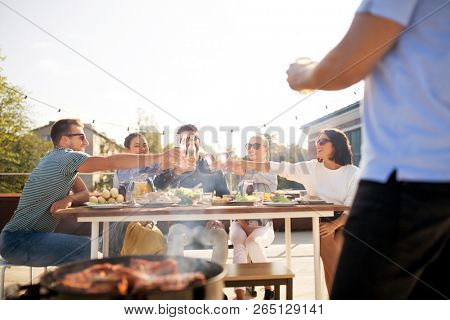 leisure and people concept - happy friends toasting drinks at barbecue party on rooftop in summer