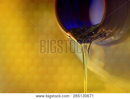 Liquid Stream Of Sweet Honey Flows From The Neck Of The Bottle Close-up.