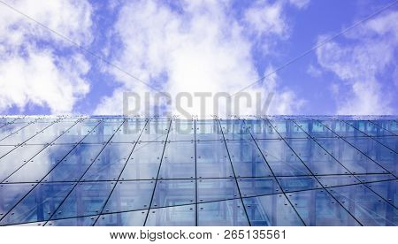 Modern glass building can accommodate offices, apartments, hotel rooms. Cloudy sky  background, under view, space.