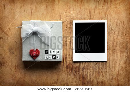 Gift box with heart and love text tied with organza ribbon and blank photo frame on old vintage wooden background.