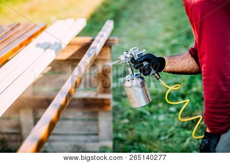 Industrial Carpenter Painting Timber With Spraygun, Outdoors