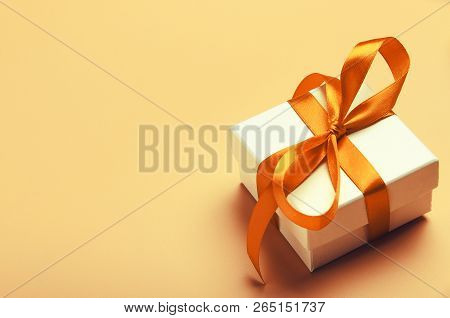 White Gift Box With Orange Bright Ribbon On Yellow Background. Beautiful Gift For The New Year, Chri