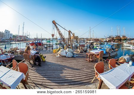 Kyrenia, Cyprus - May 12, 2018: Harbour Cafe With Fishing Boats On Background