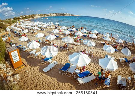 Paphos, Cyprus - August 20, 2017: Rows Of Beach Lounges And Sun Umbrellas On A Coral Bay Beach Near