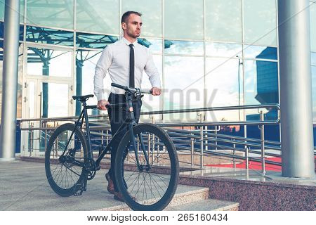Man In Suit Holding A Cup Of Coffee Walking By The Street With His Bicycle.