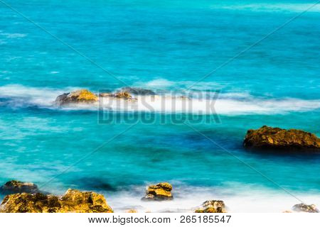Seascape Of Blue Ocean Water And Whitecaps Around Boulders Shot At Very Slow Shutter Speed And Speci
