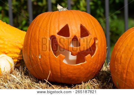 Carved Pumpkin Sitting On Hay Bail During The Day