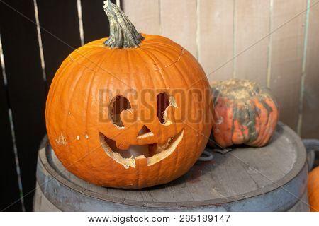 Carved Smiling Pumpkin Sitting On Barrel Outside