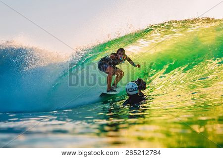 September 8, 2018. Bali, Indonesia. Surfer Ride In Barrel Wave And Surf Photographer At Sunset. Prof