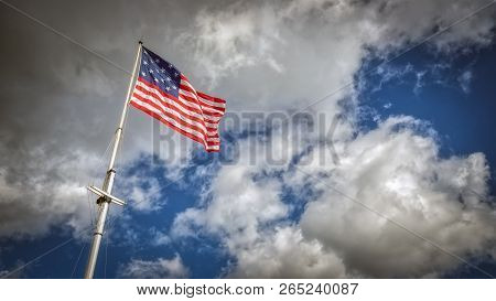 A 15 Star American Flag Flying On A Pole On A Windy Day.