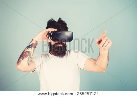Man With Beard In Vr Glasses, Light Blue Background. Interactive Surface Concept. Hipster On Busy Fa