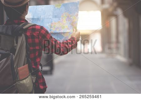 Young Man Looking In Open Map. Traveler Standing With Road Map In Hands. Hipster Backpacker Lost In
