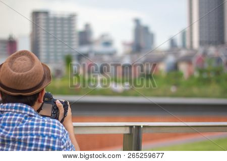 Young Asian Traveler Man Wearing Hat Taking Photo With Dslr Camera In The City With Business Zone Bu